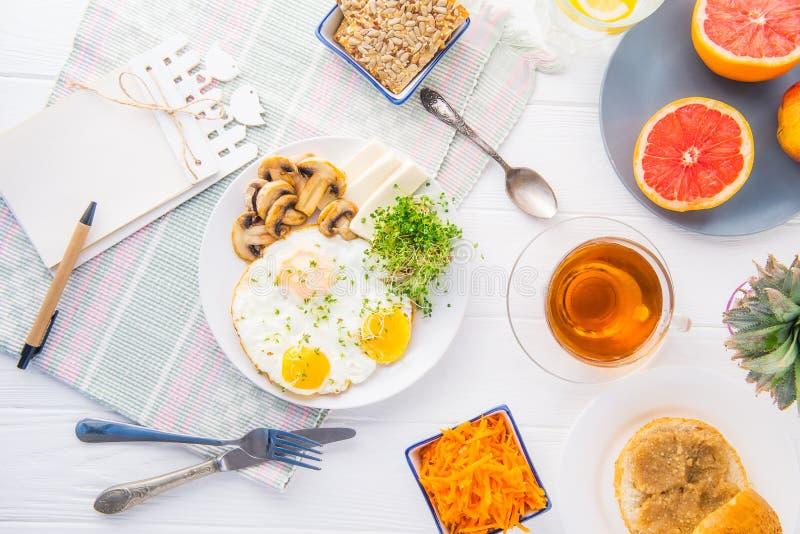 Το σημειωματάριο με τα emty κενά και το υγιές πιάτο προγευμάτων με τα ανακατωμένα αυγά, τυρί, έψησε τα μανιτάρια και τα πράσινα μ στοκ εικόνες