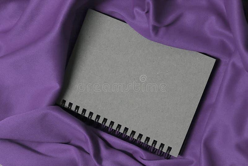 Το σημειωματάριο στο πορφυρό ύφασμα, σημειωματάριο είναι γκρίζα, εκλεκτής ποιότητας κάλυψη σημειωματάριων στοκ φωτογραφίες με δικαίωμα ελεύθερης χρήσης