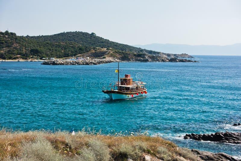 Το σκάφος πλέει στο μικρό λιμάνι Sarti, τοποθετεί Athos στο υπόβαθρο, Sithonia στοκ εικόνα