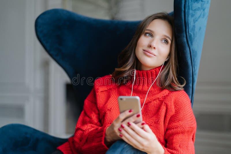 Το σκεπτικό χαριτωμένο θηλυκό αισθάνεται χαλαρωμένο, ακούει ευχάριστη μουσική στο playlist, κρατά κυψελοειδής, κοιτάζει με την ον στοκ εικόνα με δικαίωμα ελεύθερης χρήσης