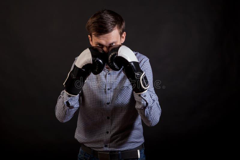 Το σκοτεινός-μαλλιαρό άτομο σε ένα πουκάμισο καρό με τα εγκιβωτίζοντας γάντια σε δικοί του παραδίδει τη θέση στοκ εικόνες