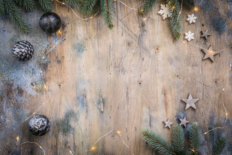 Το σκοτεινό επίπεδο Χριστουγέννων βάζει τη σύνθεση με τους κλάδους έλατου, τα αστέρια και τις μαύρες σφαίρες στο ξύλινο εκλεκτής  στοκ φωτογραφία με δικαίωμα ελεύθερης χρήσης