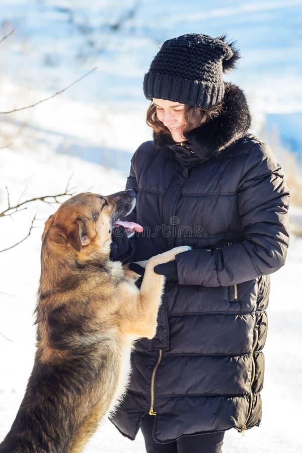 Το σκυλί στέκεται στα οπίσθια πόδια κοντά στο κορίτσι και εξετάζει το πρόσωπό της κατά τη διάρκεια του χειμώνα walk_ στοκ φωτογραφία