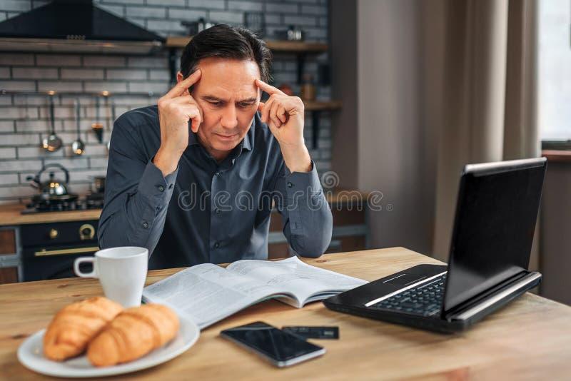Το σοβαρό άτομο κάθεται στον πίνακα στην κουζίνα και την ανάγνωση Εξετάζει κάτω τα χέρια περιοδικών και λαβής στο κεφάλι Το άτομο στοκ εικόνες