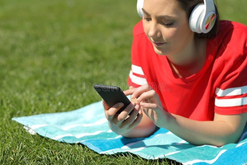Το σοβαρό κορίτσι ακούει τηλεφωνικό την περιεκτικότητα σε ξεφυλλίσματος μουσικής στη χλόη στοκ εικόνες