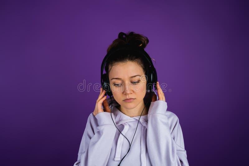 Το σοβαρό κορίτσι ακούει τη λυπημένη μουσική στα ακουστικά σε μια μπλούζα σε ένα πορφυρό υπόβαθρο στοκ εικόνες με δικαίωμα ελεύθερης χρήσης