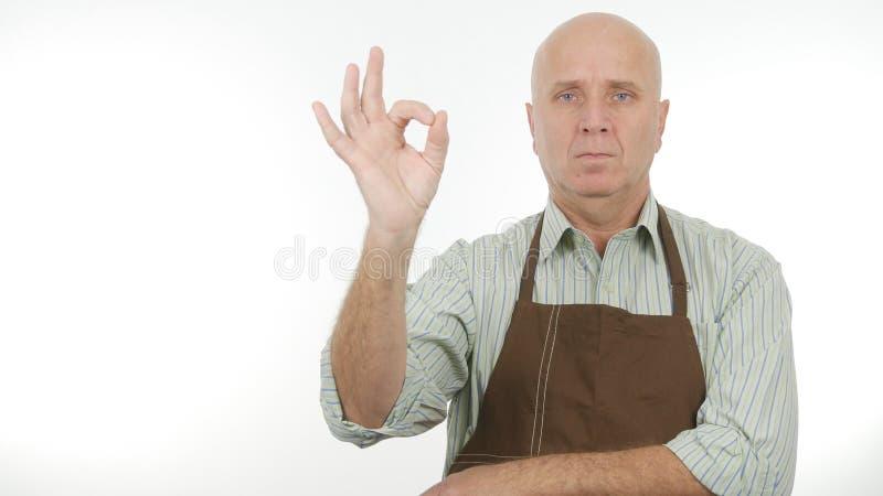 Το σοβαρό πρόσωπο που φορά την ποδιά κάνει το καλό σημάδι εργασίας τις ΕΝΤΑΞΕΙ χειρονομίες χεριών στοκ εικόνες