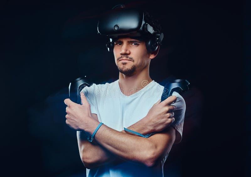 Το σοβαρό υπέρ gamer που φορά τα γυαλιά εικονικής πραγματικότητας και κρατά τα πηδάλια, που θέτουν με τα διασχισμένα όπλα στοκ φωτογραφίες