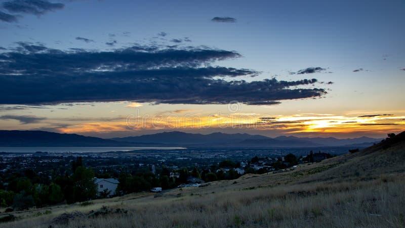 Το σούρουπο μειώνεται πέρα από μια νυσταλέα πόλη σε μια κοιλάδα με τα βουνά και μια λίμνη στο υπόβαθρο στοκ εικόνα με δικαίωμα ελεύθερης χρήσης