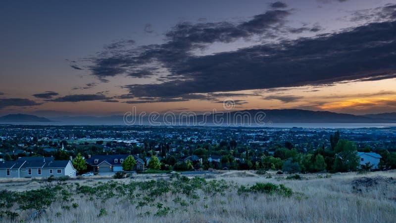 Το σούρουπο μειώνεται πέρα από μια νυσταλέα πόλη σε μια κοιλάδα με τα βουνά και μια λίμνη στο υπόβαθρο στοκ εικόνες