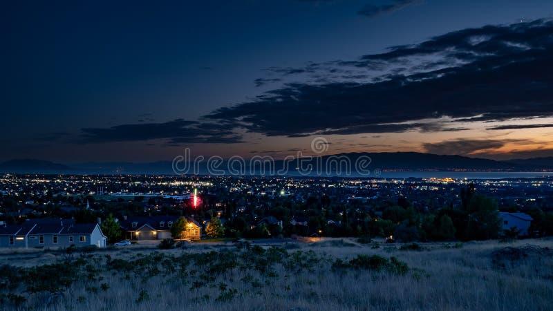 Το σούρουπο μειώνεται πέρα από μια νυσταλέα πόλη σε μια κοιλάδα με τα βουνά και μια λίμνη στο υπόβαθρο στοκ εικόνες με δικαίωμα ελεύθερης χρήσης