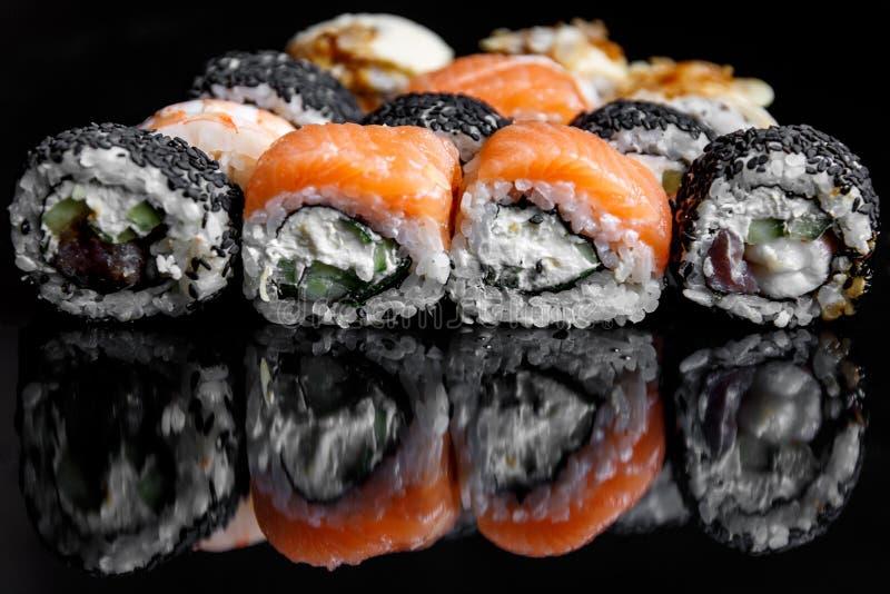 Το σούσι κυλά με το σολομό, τον τόνο, το αγγούρι και τα πράσινα κρεμμύδια στο μαύρο υπόβαθρο στοκ εικόνες