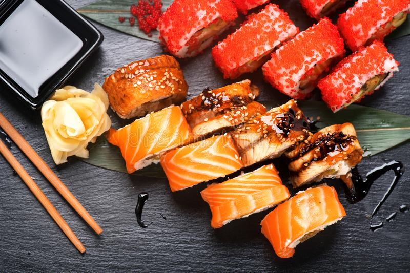 Το σούσι κυλά την κινηματογράφηση σε πρώτο πλάνο Ιαπωνικά τρόφιμα στο εστιατόριο Ρόλος με το σολομό, το χέλι, τα λαχανικά και το  στοκ φωτογραφία