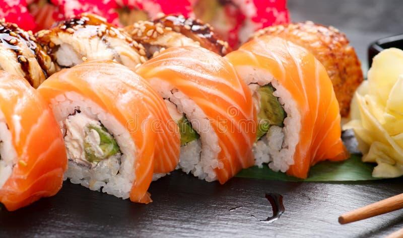 Το σούσι κυλά την κινηματογράφηση σε πρώτο πλάνο Ιαπωνικά τρόφιμα στο εστιατόριο Ρόλος με το σολομό, το χέλι, τα λαχανικά και το  στοκ φωτογραφία με δικαίωμα ελεύθερης χρήσης
