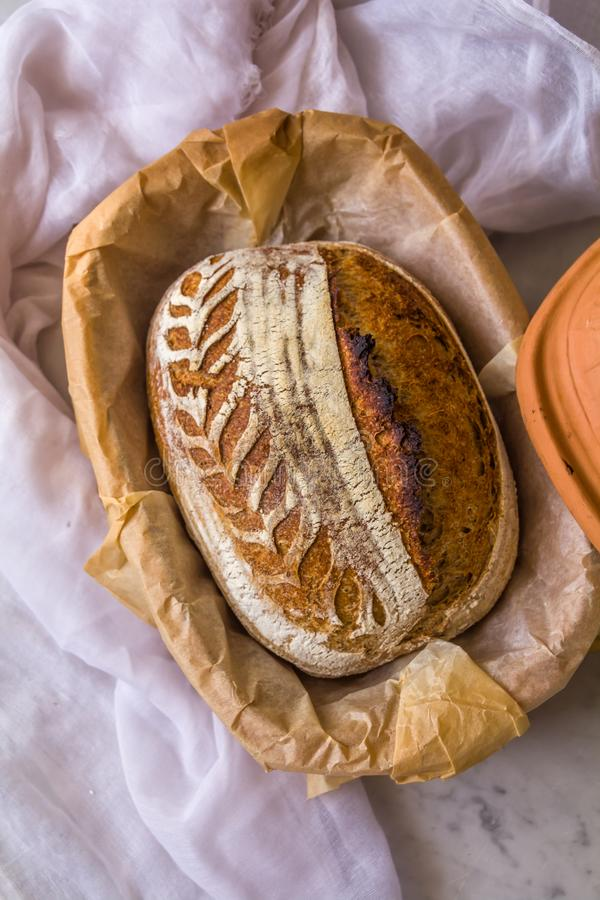 Το σπίτι έκανε την ξινή ζύμη το χειροτεχνικό συλλαβισμένο ψωμί μετά από το ψήσιμο σε έναν ολλανδικό φούρνο στο μαρμάρινο υπόβαθρο στοκ εικόνα