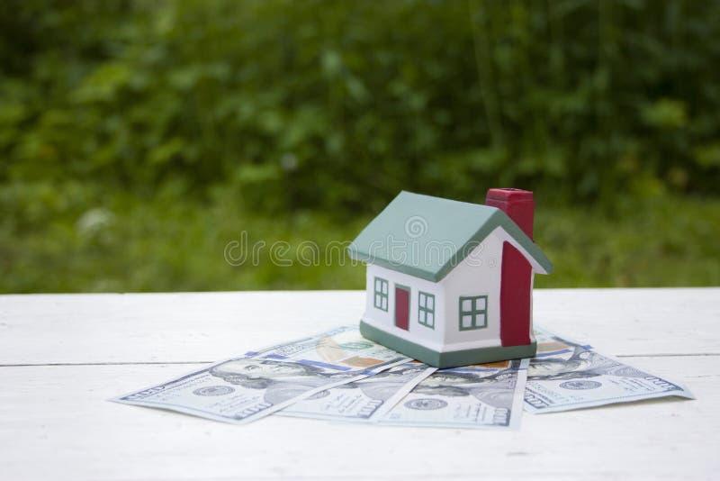 Το σπίτι αξίζει τους λογαριασμούς εκατό δολαρίων Εννοιολογική φωτογραφία στοκ εικόνες