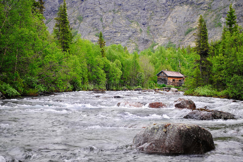 Το σπίτι στον ποταμό βουνών στοκ φωτογραφία