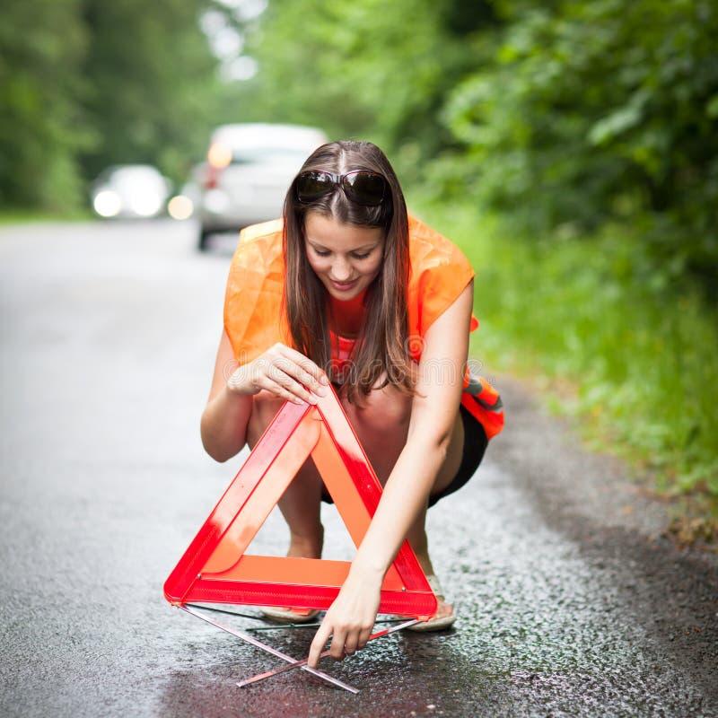 το σπασμένο αυτοκίνητο κάτω από το θηλυκό οδηγών την έχει στοκ φωτογραφίες