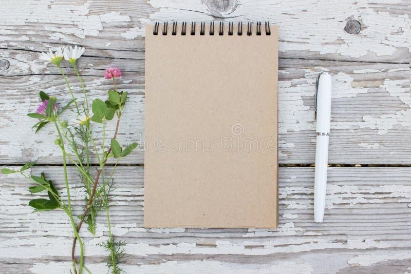Το σπειροειδές σημειωματάριο εγγράφου της Kraft, η άσπρη μάνδρα και το καλοκαίρι ανθίζουν στο αγροτικό ξύλινο υπόβαθρο Πρότυπο στοκ φωτογραφία με δικαίωμα ελεύθερης χρήσης