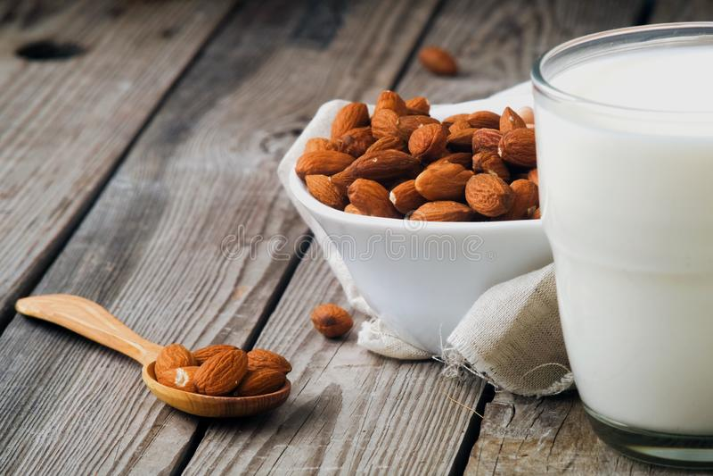 Το σπιτικό γάλα αμυγδάλων στο γυαλί, το κύπελλο και το κουτάλι με τα αμύγδαλα στον αγροτικό ξύλινο πίνακα, κλείνει επάνω στοκ εικόνες