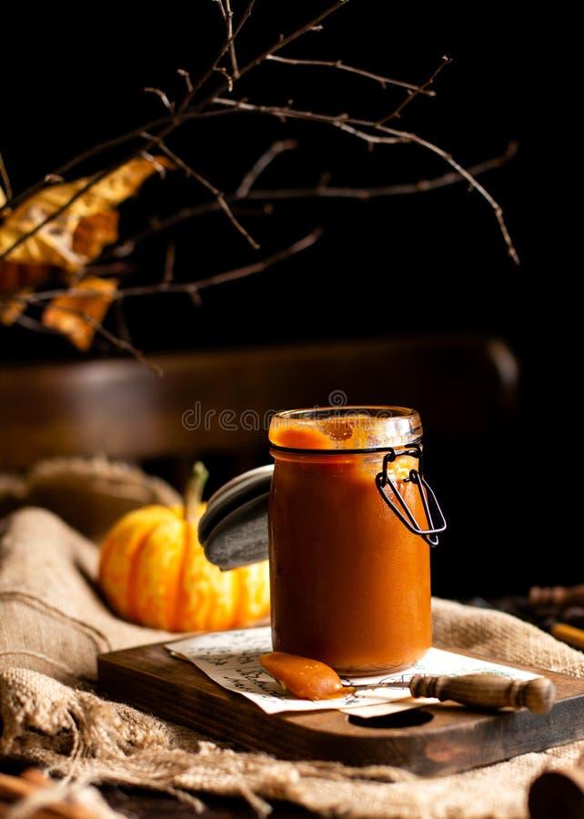 Το σπιτικό γλυκό και νόστιμο βάζο γυαλιού καραμέλας ν κολοκύθας στέκεται στον ξύλινο πίνακα στοκ εικόνες