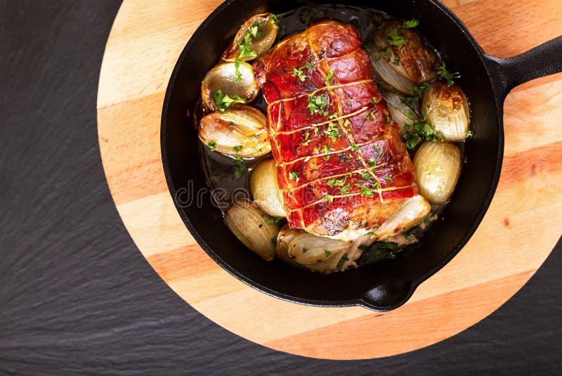 Το σπιτικό μπέϊκον έννοιας τροφίμων γέμισε Tenderloin χοιρινού κρέατος που ψήθηκε χυτό στο σίδηρος skillet στο στρογγυλό ξύλινο π στοκ εικόνες με δικαίωμα ελεύθερης χρήσης