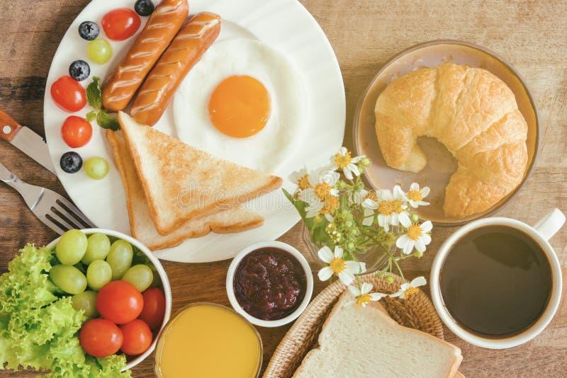 Το σπιτικό πρόγευμα με την ηλιόλουστη πλευρά τηγάνισε επάνω το λουκάνικο FR φρυγανιάς αυγών στοκ φωτογραφίες