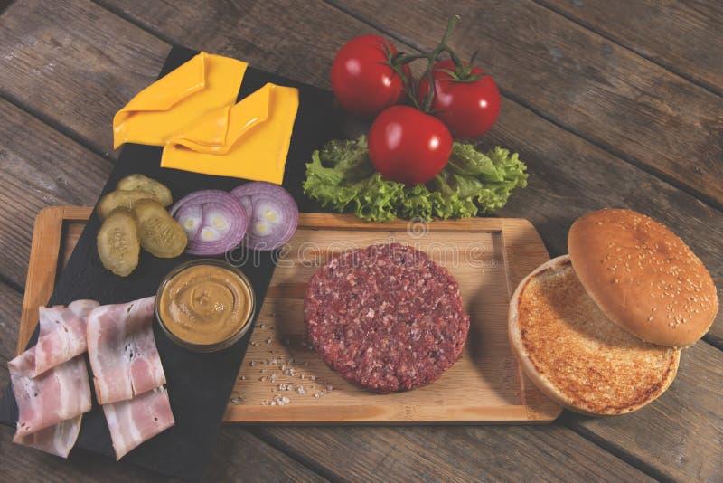 Το σπιτικό cheeseburger φρέσκο τυρί συστατικών, κουλούρι, αλάτισε το αγγούρι, patties βόειου κρέατος, μπέϊκον στοκ εικόνα με δικαίωμα ελεύθερης χρήσης