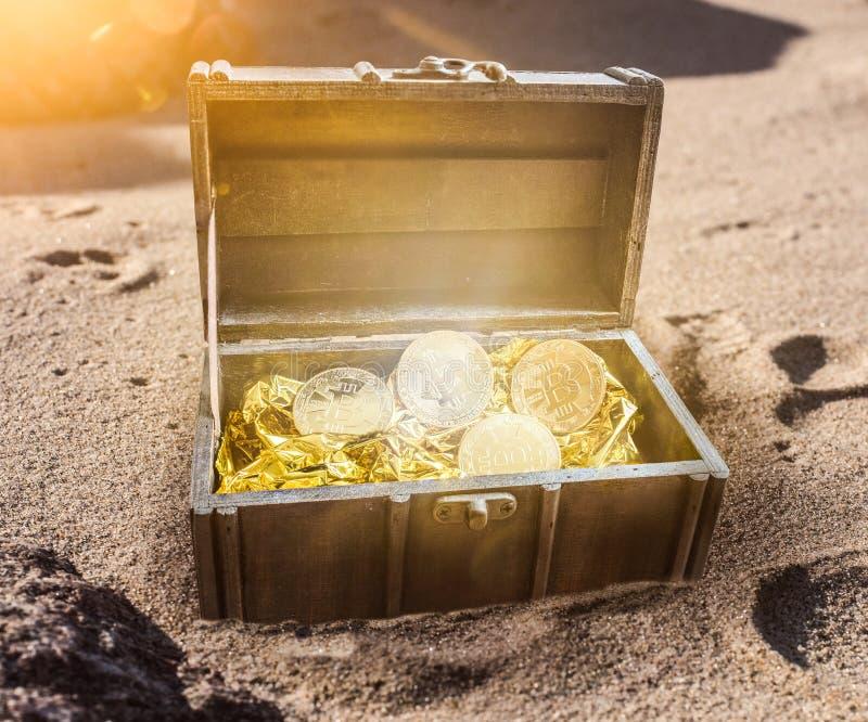 Το στήθος θησαυρών που γέμισαν με τα bitcoins που περιβλήθηκαν από τη χρυσή πυράκτωση μερικώς στην άμμο στοκ φωτογραφία