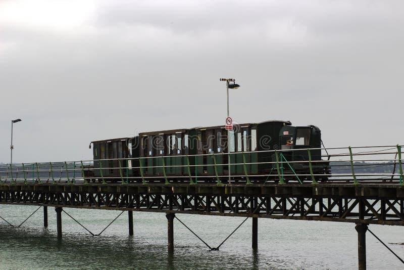 Το στενό τραίνο μετρητών που τρέχει το μήκος των φέρνοντας επιβατών αποβαθρών Hythe σε και από το πορθμείο σε Southampton που λαμ στοκ φωτογραφία με δικαίωμα ελεύθερης χρήσης