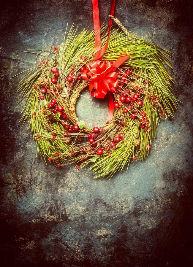 Το στεφάνι Χριστουγέννων έκανε †‹â€ ‹των κλάδων έλατου και των κόκκινων χειμερινών μούρων στο εκλεκτής ποιότητας υπόβαθρο στοκ φωτογραφίες με δικαίωμα ελεύθερης χρήσης