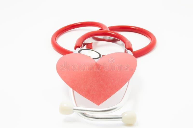 Το στηθοσκόπιο και η κόκκινη καρδιά βελούδου βρίσκονται το ένα στο άλλο στο άσπρο ομοιόμορφο υπόβαθρο Φωτογραφία για τη χρήση στη στοκ φωτογραφίες