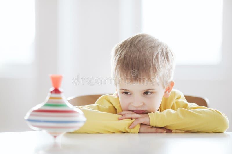 Το στοχαστικό αγόρι κάθεται στον πίνακα και εξετάζει την περιστρεφόμενη κορυφή στοκ εικόνα με δικαίωμα ελεύθερης χρήσης