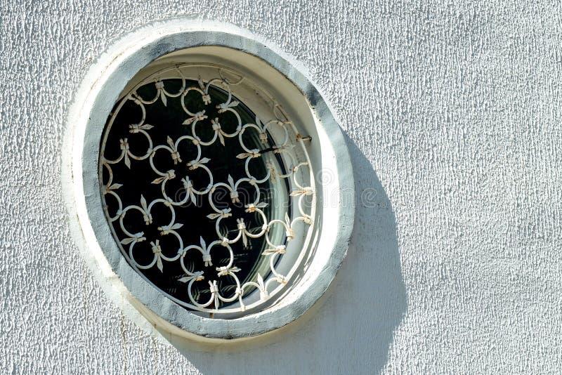 Το στρογγυλό παράθυρο με το κιγκλίδωμα επεξεργασμένου σιδήρου στοκ φωτογραφία