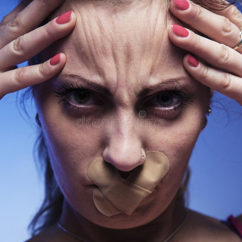 Το στόμα που σφραγίζεται που κλείνει ως σύμβολο της ανισότητας γένους, πόνος, στοκ φωτογραφίες
