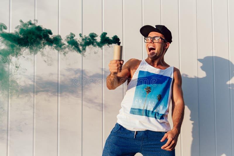Το συγκινημένο άτομο κρατά μια φλόγα καπνού ενώ έχοντας τη διασκέδαση υπαίθρια στοκ εικόνες