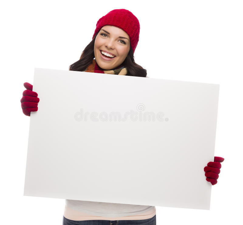 Το συγκινημένο κορίτσι που φορά το χειμερινά καπέλο και τα γάντια κρατά το κενό σημάδι στοκ εικόνα