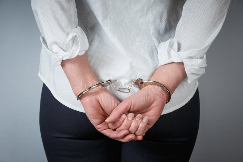 Το συλλήφθείτ άτομο έδεσε τα χέρια με χειροπέδες στην πλάτη που απομονώθηκε στο γκρίζο υπόβαθρο στοκ φωτογραφία