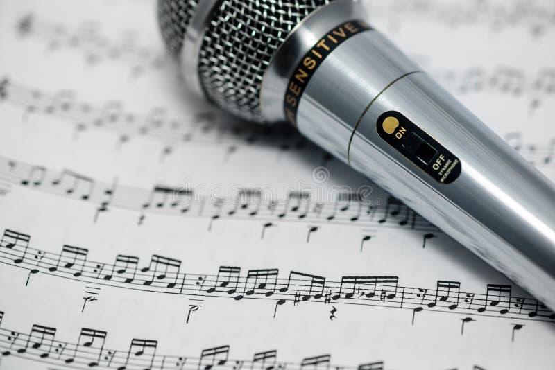 Το συμπεριλαμβανόμενο μικρόφωνο είναι στη μουσική σημείωση στοκ φωτογραφίες με δικαίωμα ελεύθερης χρήσης