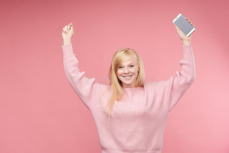 Το συναισθηματικό κορίτσι αύξησε ευτυχώς τα χέρια της επάνω στο κράτημα ενός κινητού τηλεφώνου στοκ φωτογραφία με δικαίωμα ελεύθερης χρήσης