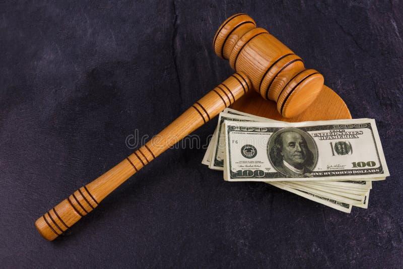 Το σφυρί δικαστών βρίσκεται σε μια στάση με έναν σωρό των δολαρίων σε ένα υπόβαθρο πετρών στοκ φωτογραφίες