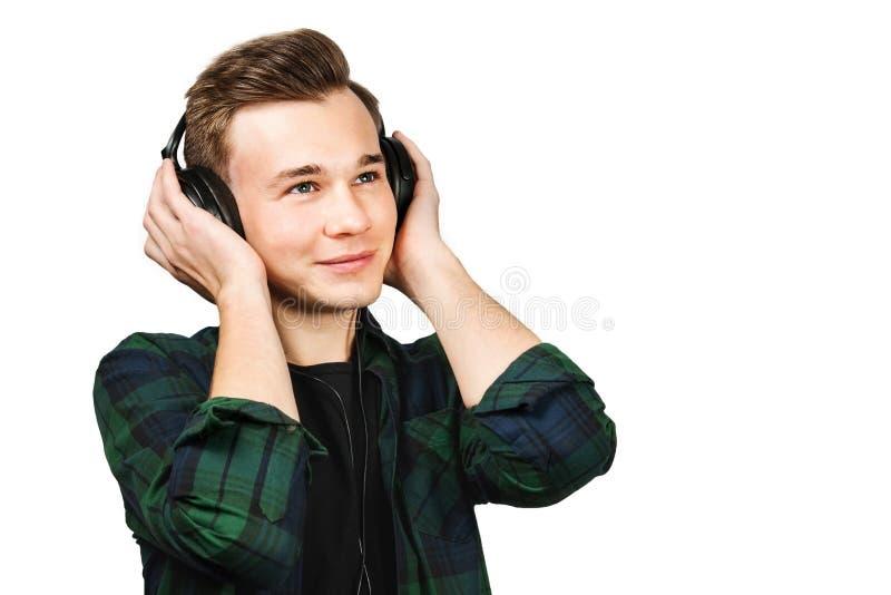 Το σχεδιάγραμμα πορτρέτου ενός καυκάσιου άσπρου νέου τύπου ακούει μουσική στα ακουστικά Το όμορφο άτομο έντυσε σε μια μαύρα μπλού στοκ φωτογραφία με δικαίωμα ελεύθερης χρήσης