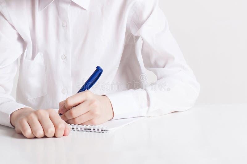 Το σχολικό αγόρι γράφει στο σημειωματάριο στον πίνακα στοκ φωτογραφία