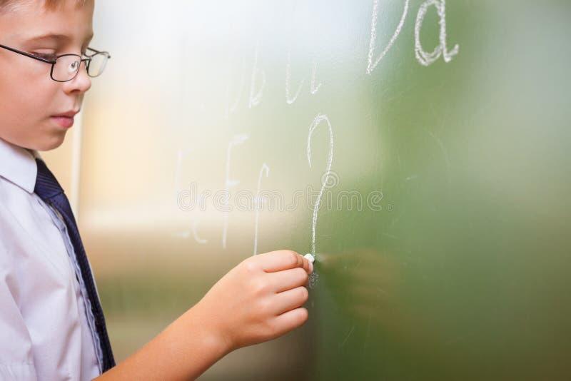 Το σχολικό αγόρι γράφει το αγγλικό αλφάβητο με την κιμωλία στον πίνακα στοκ φωτογραφία με δικαίωμα ελεύθερης χρήσης