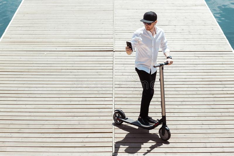 Το σύγχρονο άτομο έντυσε το άσπρο πουκάμισο και τα μαύρα εσώρουχα χρησιμοποιώντας το τηλέφωνό του στεμένος σε μια ξύλινη αποβάθρα στοκ φωτογραφία