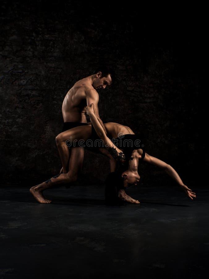 Το σύγχρονο ζεύγος χορευτών μπαλέτου στο μαύρο στοιχείο χορού τέχνης προς θέαση μορφής με το κενό διαστημικό υπόβαθρο αντιγράφων, στοκ φωτογραφία