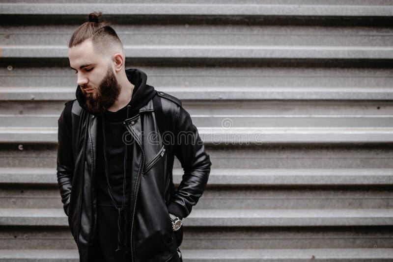 Το σύγχρονο νέο γενειοφόρο άτομο στο μαύρο ύφος ντύνει τη στάση γύρω από το αστικό υπόβαθρο στοκ φωτογραφία