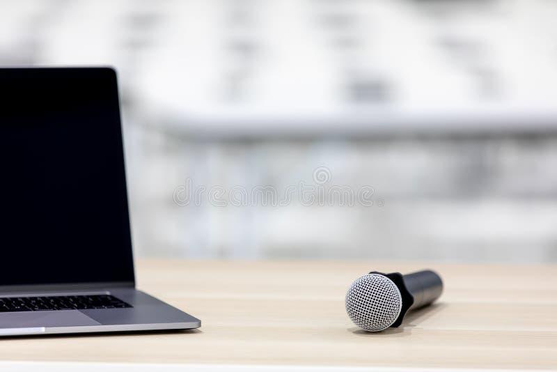 Το σύγχρονο σημειωματάριο τοποθετείται στο ξύλινο γραφείο Με το μικρόφωνο και τις δημόσιες σχέσεις στοκ φωτογραφίες