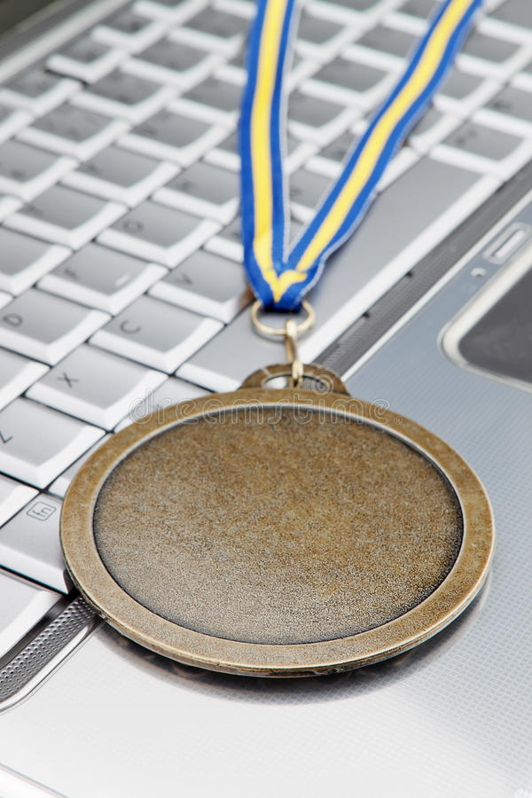 Το σύγχρονο lap-top και απονέμει ένα χρυσό μετάλλιο για την επιτυχία. στοκ φωτογραφία
