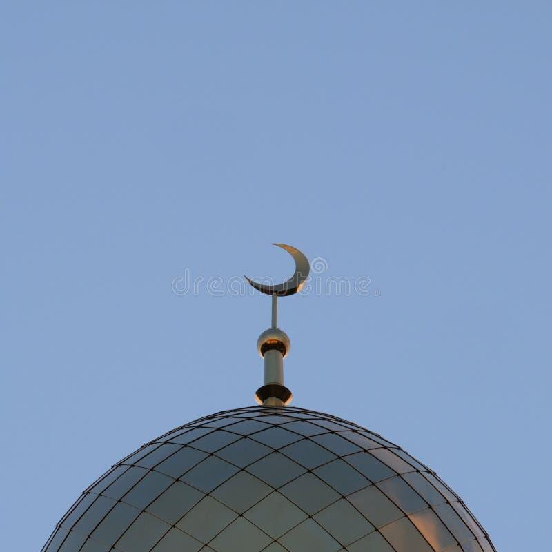 Το σύμβολο του Ισλάμ είναι ένα χρυσό ημισεληνοειδές φεγγάρι πάνω από το μιναρές μουσουλμανικών τεμενών Μπλε ουρανός βραδιού ή πρω στοκ φωτογραφίες
